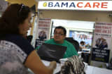 Martha Lucia (L) sits with Rudy Figueroa, an insurance agent from Sunshine Life and Health Advisors, as she picks an insurance plan available in the third year of the Affordable Care Act at a store setup in the Mall of the Americas on November 2, 2015 in M