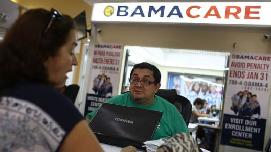 Martha Lucia (L) sits with Rudy Figueroa, an insurance agent from Sunshine Life and Health Advisors, as she picks an insurance plan available in the third year of the Affordable Care Act at a store setup in the Mall of the Americas on November 2, 2015 in Miami, Florida.