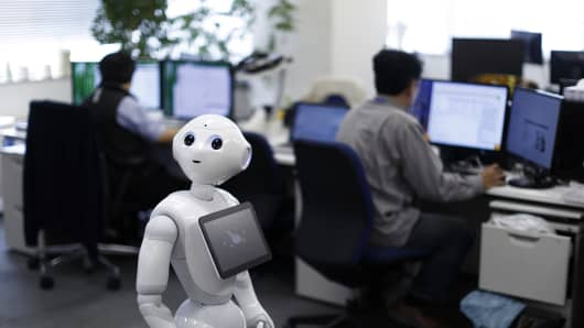 Pepper the humanoid robot, manufactured by SoftBank Group Corp., stands as employees work in the Orange Arch Inc. offices in Tokyo, Japan.