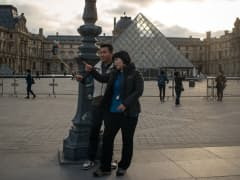 A couple of Korean tourists pose for a selfie outside the main entrance of the Louvre musem on November 15, 2015 in Paris, France.