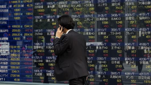 A pedestrian walks in front of a share prices board showing the numbers on the Nikkei 225 at the Tokyo Stock Exchange in Tokyo.