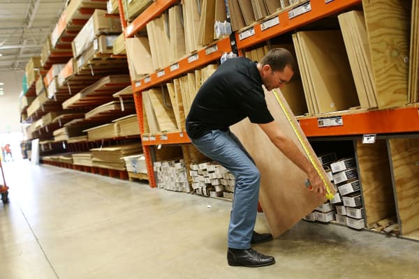 A shopper measures a piece of plywood at a Home Depot in Miami.