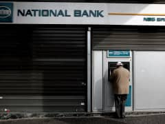 A man withdraws cash from an ATM outside a National Bank branch in Athens