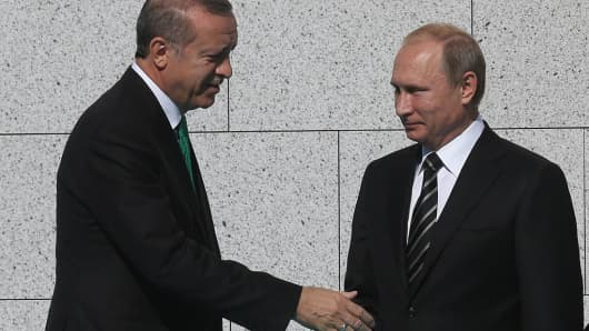 Russian President Vladimir Putin (C) greets Turkish President Tayyip Erdogan (L) during an opening ceremony for the newly restored Moscow Cathedral Mosque on September 23, 2015.