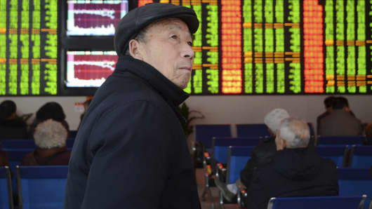 An investor looks at an electronic board showing stock information in Fuyang, China, November 27, 2015.