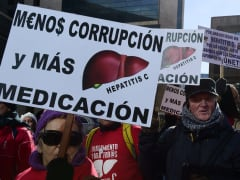 Hepatitis C sufferers and supporters hold placards during a demonstration outside of US laboratory Gilead Sciences office in Madrid on February 5, 2015. The arrival in Europe of better but pricier hepatitis C drugs has raised pressure on Spanish leaders ov