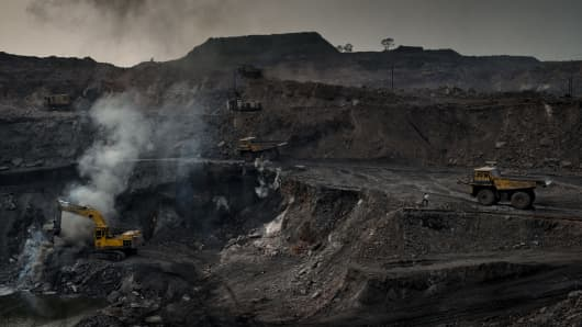 Excavators take a break as fire and smoke spew out of the ground in one of the coal mines in Jharia. Jharia in India's eastern Jharkand state is literally in flames.