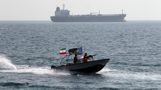 Iranian Revolutionary Guards drive a speedboat in front of an oil tanker at the port of Bandar Abbas.