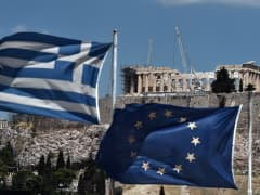 An EU and a Greek flag wave in front of the ancient temple of Parthenon atop the Acropolis hill in Athens