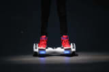 A youth poses as he rides a hoverboard, which are also known as self-balancing scooters and balance boards,