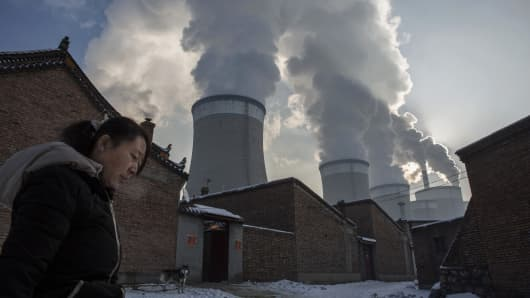 A Chinese resident walks out of her house her house next to a coal fired power plant on November 26, 2015 in Shanxi, China.
