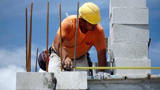 A construction worker builds a wall of a home at a Lennar development in Doral, Florida.