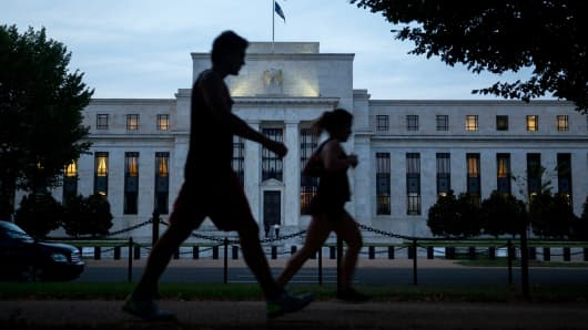 Pedestrians walk past the Federal Reserve building in Washington.