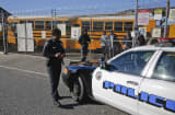 A Los Angeles School Police officer checks-in with officials at the LAUSD Gardena Garage where the fleet of school buses from around the district remian parked while law enforcement investigate a threat against the district December 15, 2015.