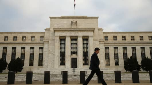A man walks past the Federal Reserve in Washington, D.C., December 16, 2015.