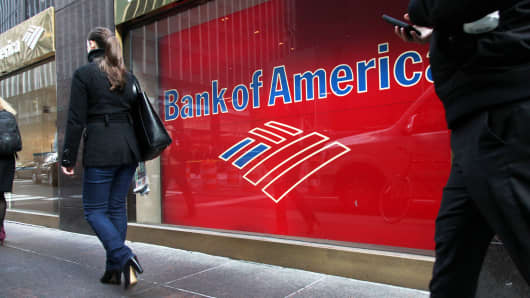 Pedestrians pass in front of a Bank of America branch in New York City.