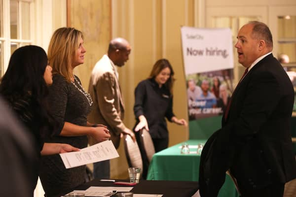 A job seeker, right, meets with recruiters during the HireLive Career Fair in San Francisco.