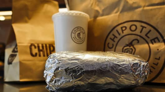 A steak burrito with a drink and bags of chips at a Chipotle Mexican Grill Inc.