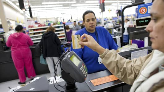 A shopper uses a credit card to pay for her items at a Wal-Mart Supercenter in Denver, Colorado.