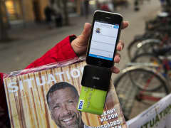 Nina Galata displays her smartphone equipped with a card reader to accept donations and payment for Situation Stockholm, Stockholms homeless magazine.