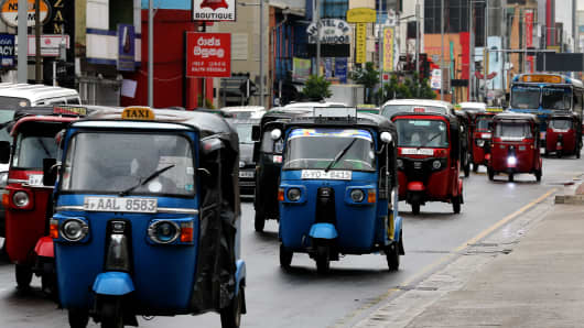 The famous Sri Lankan budget taxi, a three wheeler, drives through traffic in Colombo