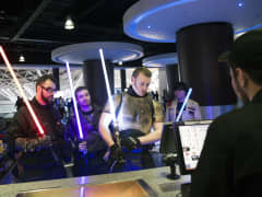 Customers holding lightsabers and dressed as Jedi Knights, collect their tickets from the counter at the first public screening of Walt Disney Co.'s 'Star Wars: The Force Awakens' at a Vue Entertainment Ltd. cinema in London, U.K