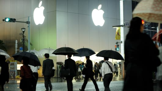 Shoppers walk past the Apple store at the high-end shopping district of Ginza in Tokyo, Japan.
