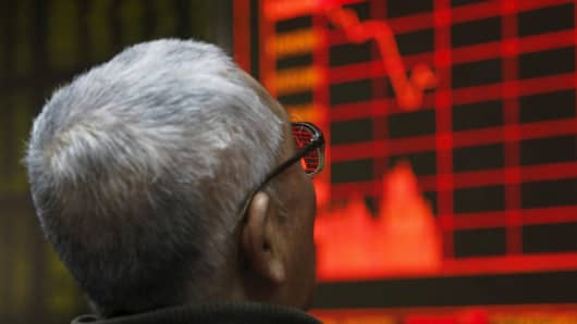 A man looks at an electronic board showing stock information at a brokerage house in Beijing, China, January 4, 2016.