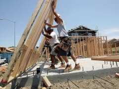 Construction workers raise wood framing as they build homes in a new housing development in Richmond, California.