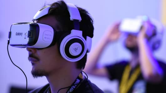 People play with virtual reality head gear 'Gear VR' of Oculus during the Tokyo Game Show.