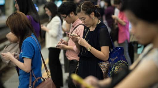 People using their smartphones in a Bangkok train station
