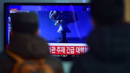 People watch a news report on North Korea's first hydrogen bomb test at a railroad station in Seoul on January 6, 2016. South Korea 'strongly' condemned North Korea's shock hydrogen bomb test and vowed to take 'all necessary measures' to penalise its nuclear-armed neighbour. The image shown on TV shows files images from other nuclear tests from other countries.
