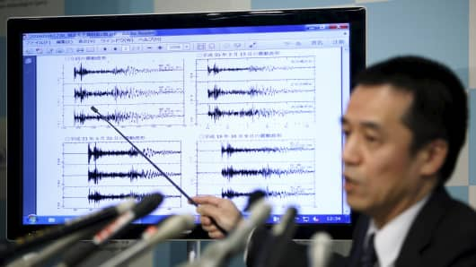 Japan Meteorological Agency's earthquake and tsunami observations division director Yohei Hasegawa points at a graph of ground motion waveform data observed in Japan during a news conference at the Japan Meteorological Agency in Tokyo on implications that an earthquake sourced around North Korea was triggered by an unnatural reason January 6, 2016.