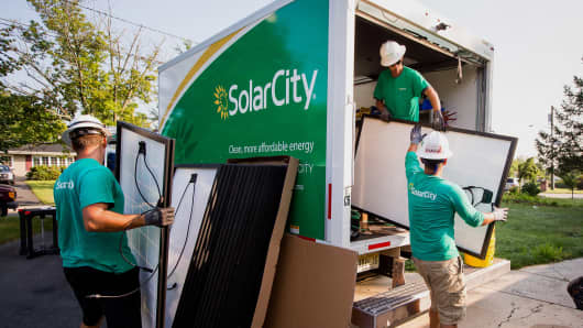 SolarCity employees unload solar panels from a truck during a home installation in Kendall Park, New Jersey.