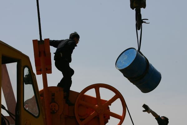 Chinese laborers repair an oil pumping unit at Huabei oil field.