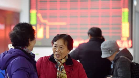 Investors play card at a stock exchange hall on January 7, 2016 in Tongling, Anhui Province of China. Chinese shares slumped to a halt in half an hour on Thursday which was the second halt in the four trading days of 2016. The Shanghai Composite Index fell 245.96 points, or 7.32 percent, to halt at 3,115.89 points.