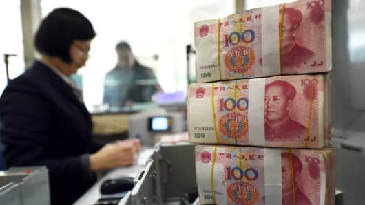 An employee counts 100-yuan (15 USD) banknotes at a bank in Lianyungang, in eastern China's Jiangsu province on January 7, 2016. China weakened the value of its yuan currency by 0.51 percent to 6.5646 against the US dollar on January 7, figures from the China Foreign Exchange Trade System showed.