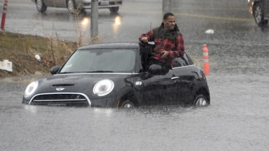 A driver climbs out of a window of his car after driving onto a flooded road in Van Nuys, Calif., on Jan. 5, 2016.
