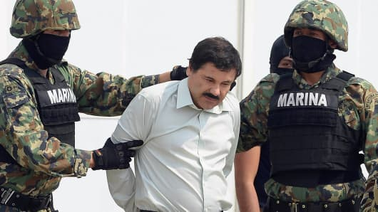 Mexican drug trafficker Joaquin Guzman Loera aka 'el Chapo Guzman' (C), is escorted by marines as he is presented to the press on February 22, 2014 in Mexico City.