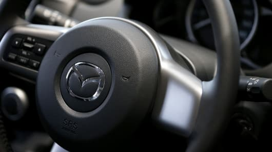 The Mazda Motor Corp. logo is displayed on the steering wheel. Mazda Motor Corp said Friday it will recall 374,000 U.S. vehicles linked to potentially defective front passenger- side airbags made by Takata Corp.