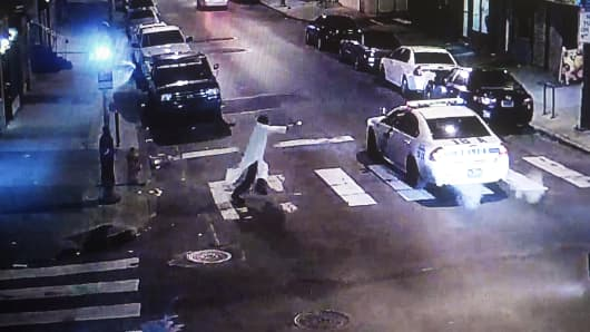 A photograph of a video survelliance image shows Edward Archer  approaching police officer Jesse Hartnett's patrol car. Hartnett was shot 13 times at close range.