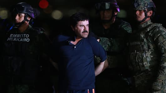 Joaquin Guzman, the world's most wanted-drug trafficker, is escorted by Mexican security forces at a Navy hangar in Mexico City, on Friday.