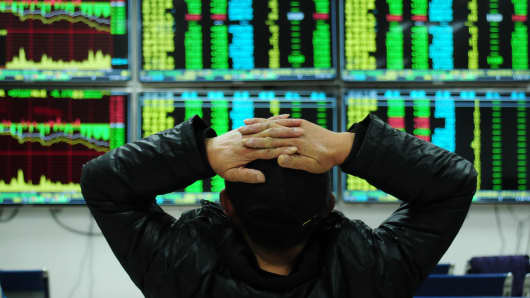 An investor watches the electronic board at a stock exchange hall on January 11, 2016 in Jiujiang, China.