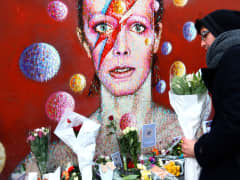 A man leaves flowers at a mural of David Bowie in Brixton on January 11, 2016 in London, England. British music and fashion icon David Bowie died earlier today at the age of 69 after a battle with cancer.