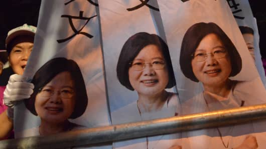 A supporter stands next to campaign flags of Tsai Ing-wen, presidential candidate for Taiwan's main opposition Democratic Progressive Party (DPP), during a rally in southern Kaohsiung on January 9, 2016.