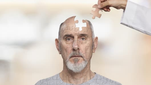 Senior man with puzzle pieces in head