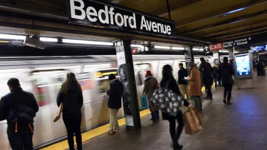 Commuters at the Bedford Ave subway station as the L train arrives in New York.