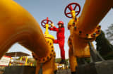 A Chinese worker checks the valve of a gas pipe at a natural gas plant in Suining, in southwest China's Sichuan province