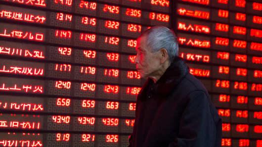 An investor walks past an electronic screen showing stock information at a brokerage house in Nanjing, Jiangsu province, January 19, 2016.