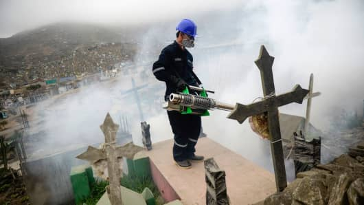 A specialist fumigates a graveyard in the outskirts of Lima, Peru on January 15, 2016. Health officials fumigated the cemetery in Peru to help prevent the Chikunguya and Zika virus, which affects several South American countries.